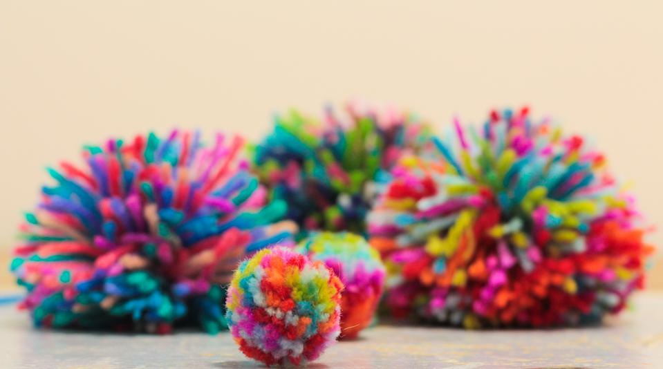 Home made rainbow pom-poms sitting in a cluster