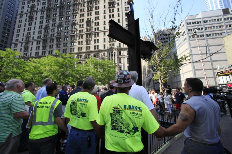 FILE - In this July 23, 2012 photo, World Trade Center construction workers hold hands during a prayer at a ceremony for the September 11 cross,  in New York. A judge should toss out a lawsuit by a national atheists group seeking to stop display of the cross-shaped steel beam found among trade center wreckage, lawyers for the operators of the Sept. 11 memorial at ground zero say. The lawyers said in papers filed in U.S. District Court in Manhattan on Monday, Aug. 13, 2012 that the 17-foot-tall beam will be displayed as a historical object because it tells part of the story of the Sept. 11, 2001, rescue and recovery effort. (AP Photo/Mark Lennihan, File)