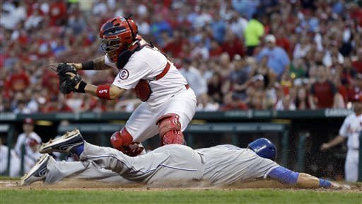 Kansas City Royals' Alex Gordon, front, scores on a sacrifice fly by Lorenzo Cain ahead of the tag from St. Louis Cardinals catcher Yadier Molina during the fourth inning of a baseball game Wednesday, May 29, 2013, in St. Louis. (AP Photo/Jeff Roberson)