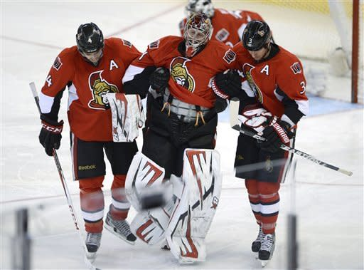 Ottawa Senators goalie Craig Anderson is help off the ice by teammates Chris Phillips (4) and Marc Methot (3) after being taken down by New York Rangers' Chris Kreider during the third period of an NHL hockey game in Ottawa, Ontario, Thursday, Feb. 21, 2013. (AP Photo/The Canadian Press, Adrian Wyld)