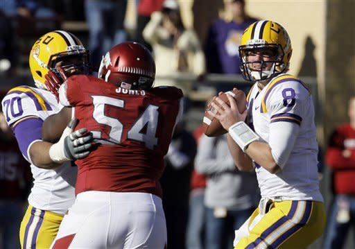 LSU quarterback Zach Mettenberger (8) prepares to pass as teammate guard La'el Collins (70) blocks Arkansas defensive tackle Byran Jones (54) during the first half of an NCAA college football game in Fayetteville, Ark., Friday, Nov. 23, 2012. (AP Photo/Danny Johnston)