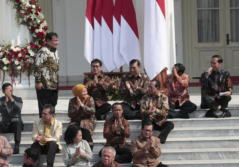 Newly appointed Defense Minister Prabowo Subianto, who is the former rival of Indonesian President Joko Widodo in last April's election, stands up as he is introduced by Widodo, right, during the announcement of the new cabinet at Merdeka Palace in Jakarta, Indonesia, Wednesday, Oct. 23, 2019. (AP Photo/Dita Alangkara)
