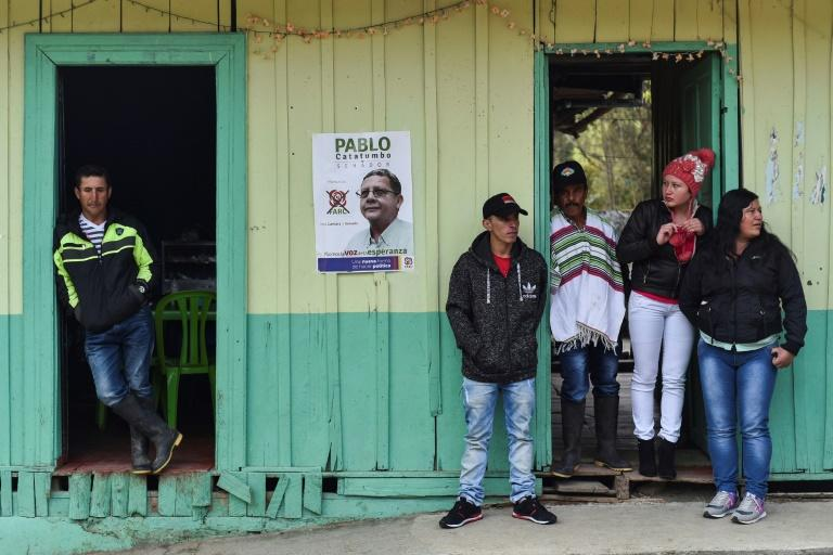 People look on as senate candidate Pablo Catatumbo and deputy candidate Marcos Calarca, both from the Common Alternative Revolutionary Force (FARC) political party, campaign in Santa Lucia, Valle del Cauca Department, Colombia, on February 25, 2018