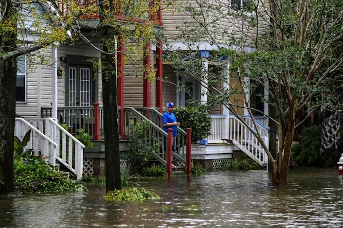 A man stands outside his home on a street flooded by Hurricane Sally in Pensacola, Florida, on September 16, 2020