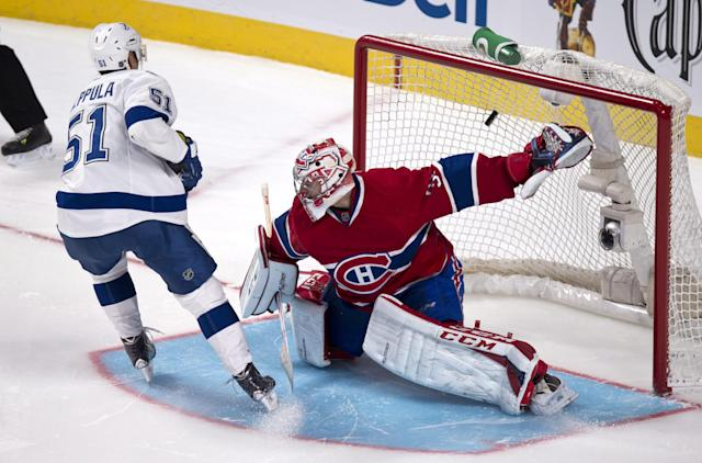 Tampa Bay Lightning's Valtteri Filppula scores past Montreal Canadiens goalie Carey Price in the shootout during an NHL hockey game Tuesday, Nov. 12, 2013, in Montreal. The Lightning won 2-1. (AP Photo/The Canadian Press, Paul Chiasson)