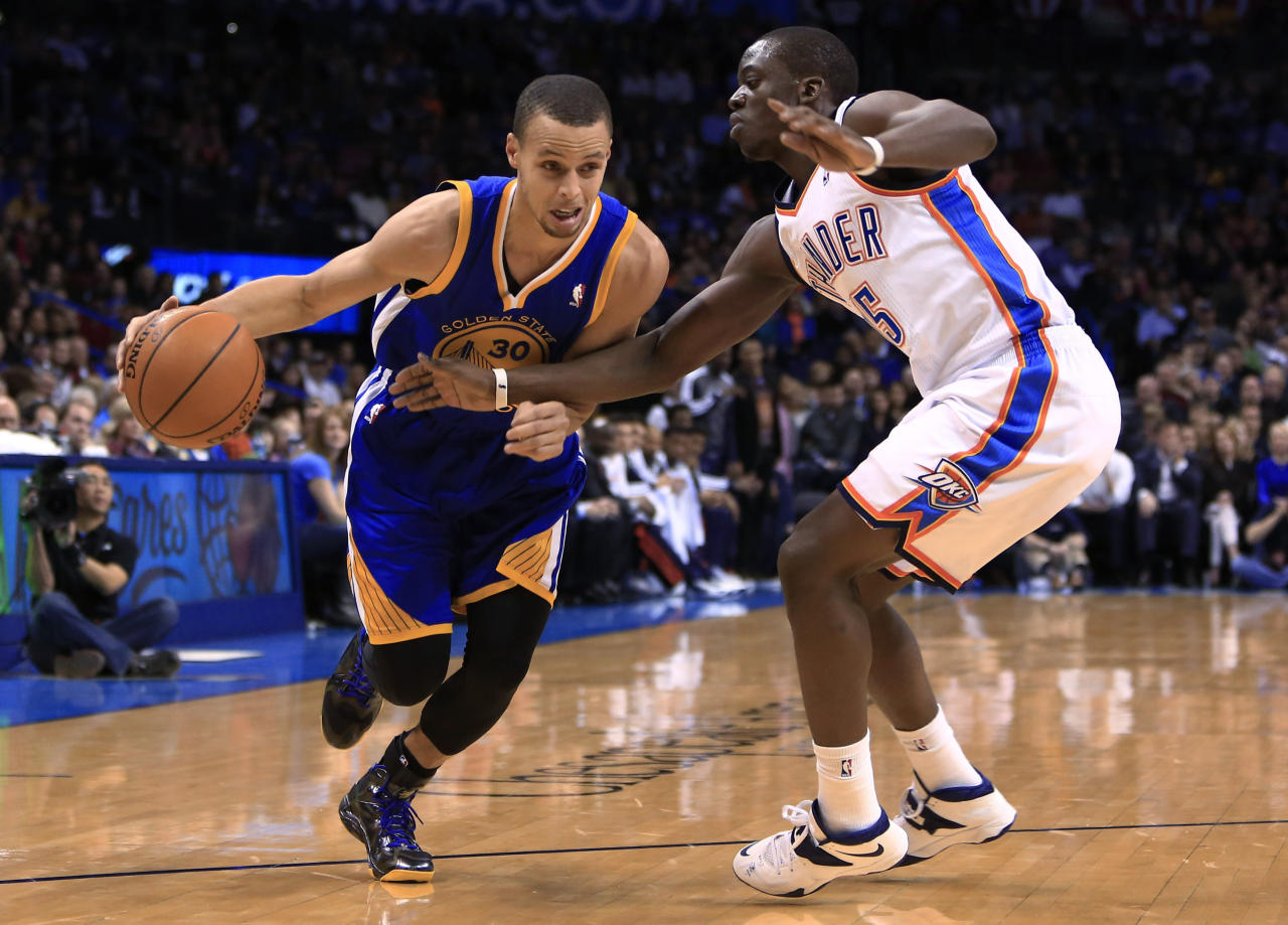 Golden State Warriors point guard Stephen Curry (30) drives to the basket around Oklahoma City Thunder guard Reggie Jackson (15) during the first quarter of an NBA basketball game Friday, Jan. 17, 2014, in Oklahoma City. (AP Photo/Alonzo Adams)
