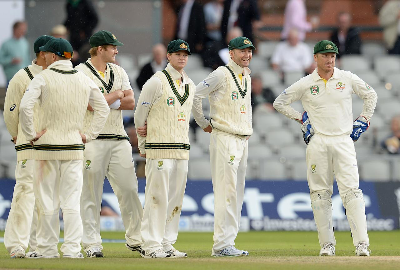 Australia's Michael Clarke (second right) can only smile as rain stops play, during day five of the Third Investec Ashes test match at Old Trafford Cricket Ground, Manchester.
