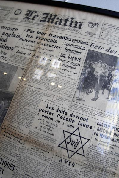 """In this photo taken Monday, July 16, 2012 shows the front page of daily newspaper Le Matin reading """"Jews must wear the yellow star starting July 7"""" coming from the Archives of Paris Police Prefecture is presented for an exhibition of French archives on Shoah in Paris. The chilling archives of the biggest World War II deportation of French Jews are being opened up to public view for the first time. It coincides with the 70th anniversary of the Vel' d'Hiv roundup by Paris police of some 13,000 Jews over two days who were then sent to Auschwitz death camp. Photos, signatures and records of personal possessions from many of the victims are on display at a Paris district town hall. (AP Photo/Remy de la Mauviniere)"""
