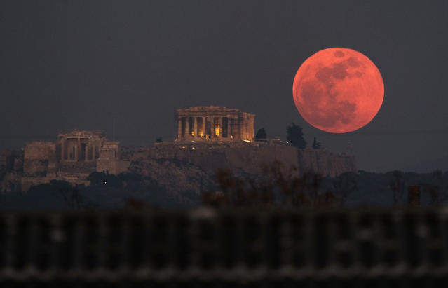A super blue blood moon rises behind the 2,500-year-old Parthenon temple on the Acropolis of Athens, Greece, on Wednesday, Jan. 31, 2018. On Wednesday, much of the world got to see not only a blue moon which is a supermoon, but also a lunar eclipse, all rolled into one celestial phenomenon. (AP Photo/Petros Giannakouris)