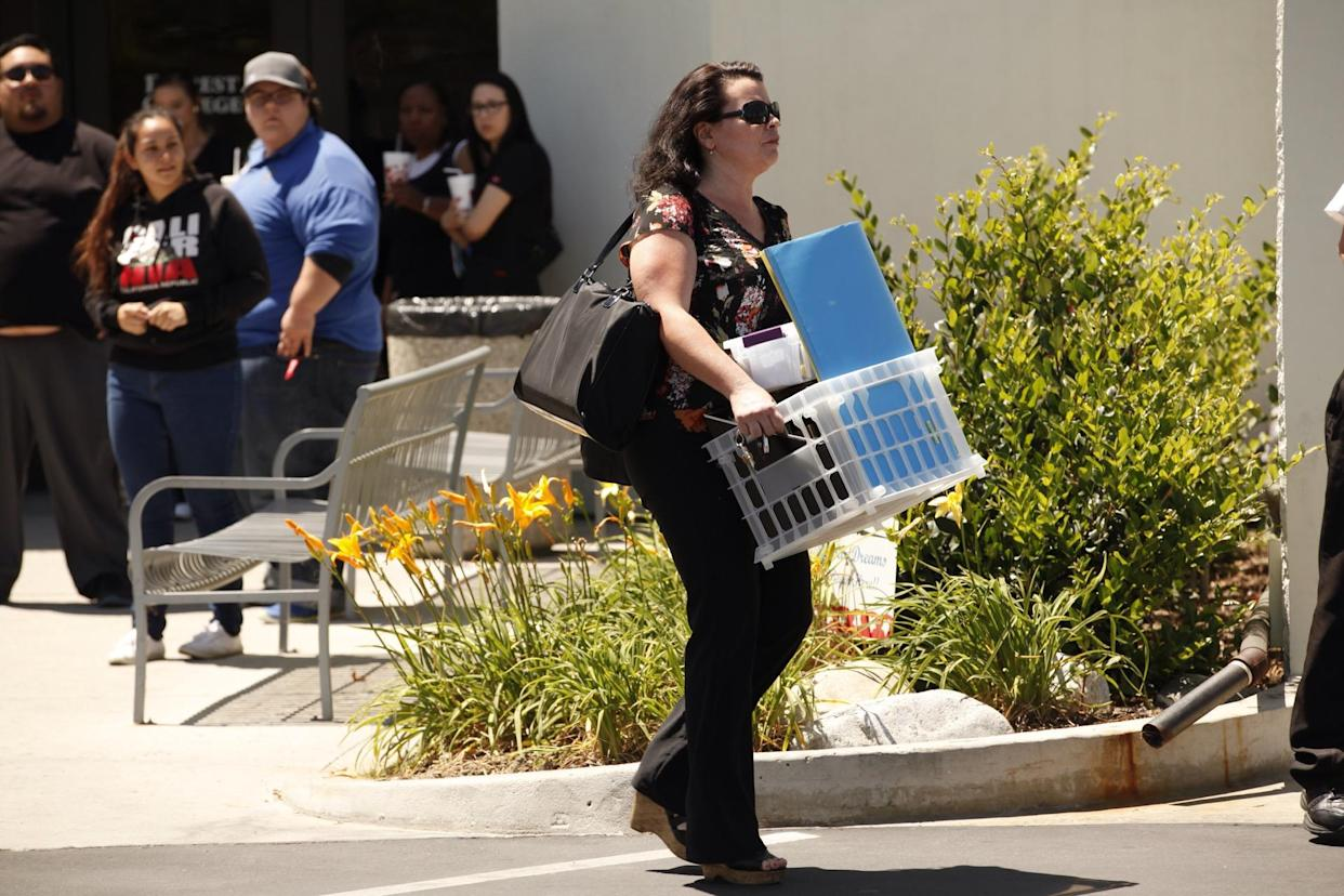 A teacher carries her belongings out from one of the Corinthian Colleges that closed in 2015. (Photo: Al Seib / Los Angeles Times / Getty Images)