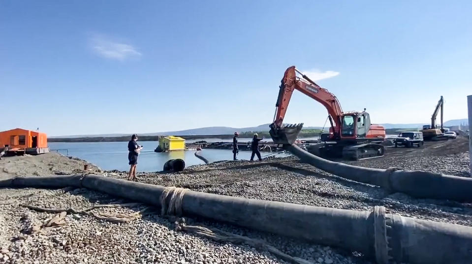 In this photo released Sunday June 28, 2020, by Novaya Gazeta, showing what the report is an excavator disassembling a pipe from a Norilsk Nickel enrichment plant with water gushing into a river which also runs into the lake near Norilsk, 2,900 kilometers (1,800 miles) northeast of Moscow, Russia. Russia's main criminal investigation body has launched a probe after a report that a nickel-processing plant was pumping water contaminated with heavy metals into the Arctic tundra. (Elena Kostyuchenko, Novaya Gazeta via AP)