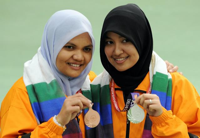 Bronze medalist Mohamed Taibi Nur Suryani (L) and silver medalist Halim Nur Ayuni of Malaysia pose after the medal ceremony of the women's singles 10m air rifle event at the Karni Singh shooting range in New Delhi on October 10, 2010. The Commonwealth Games are taking place in the Indian capital from October 3-14. AFP PHOTO/Indranil MUKHERJEE (Photo credit should read INDRANIL MUKHERJEE/AFP/Getty Images)
