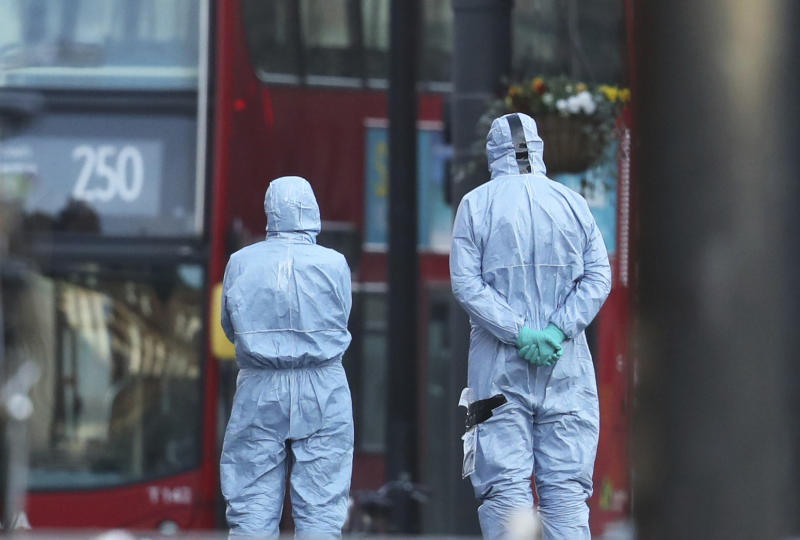 Police forensic officers work at the scene following a terror stabbing attack in the Streatham area of south London Monday Feb. 3, 2020. Police in London say the man identified as 20-year-old Sudesh Amman was wearing a fake bomb and stabbed two people Sunday before being shot to death by police was recently released from prison, where he was serving for terrorism offenses.(Aaron Chown/PA via AP)