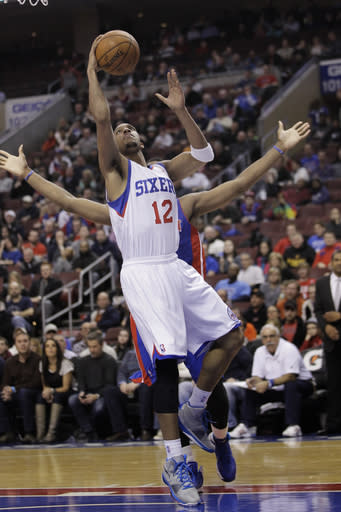 Philadelphia 76ers' Evan Turner (12) is followed to the basket by Detroit Pistons' Andre Drummond in the second half of an NBA basketball game on Friday, Jan. 10, 2014, in Philadelphia. The Pistons won 104-114. (AP Photo/Laurence Kesterson)