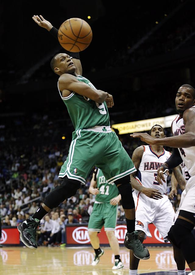 Boston Celtics' Rajon Rondo, left, loses control of the ball while going up for a shot against Atlanta Hawks' Paul Millsap, right, in the fourth quarter of an NBA basketball game, Wednesday, April 9, 2014, in Atlanta. The Hawks won 105-97. (AP Photo/David Goldman)