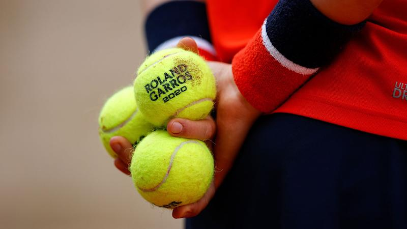 Pictured here, a ball person holds tennis balls during a French Open match.