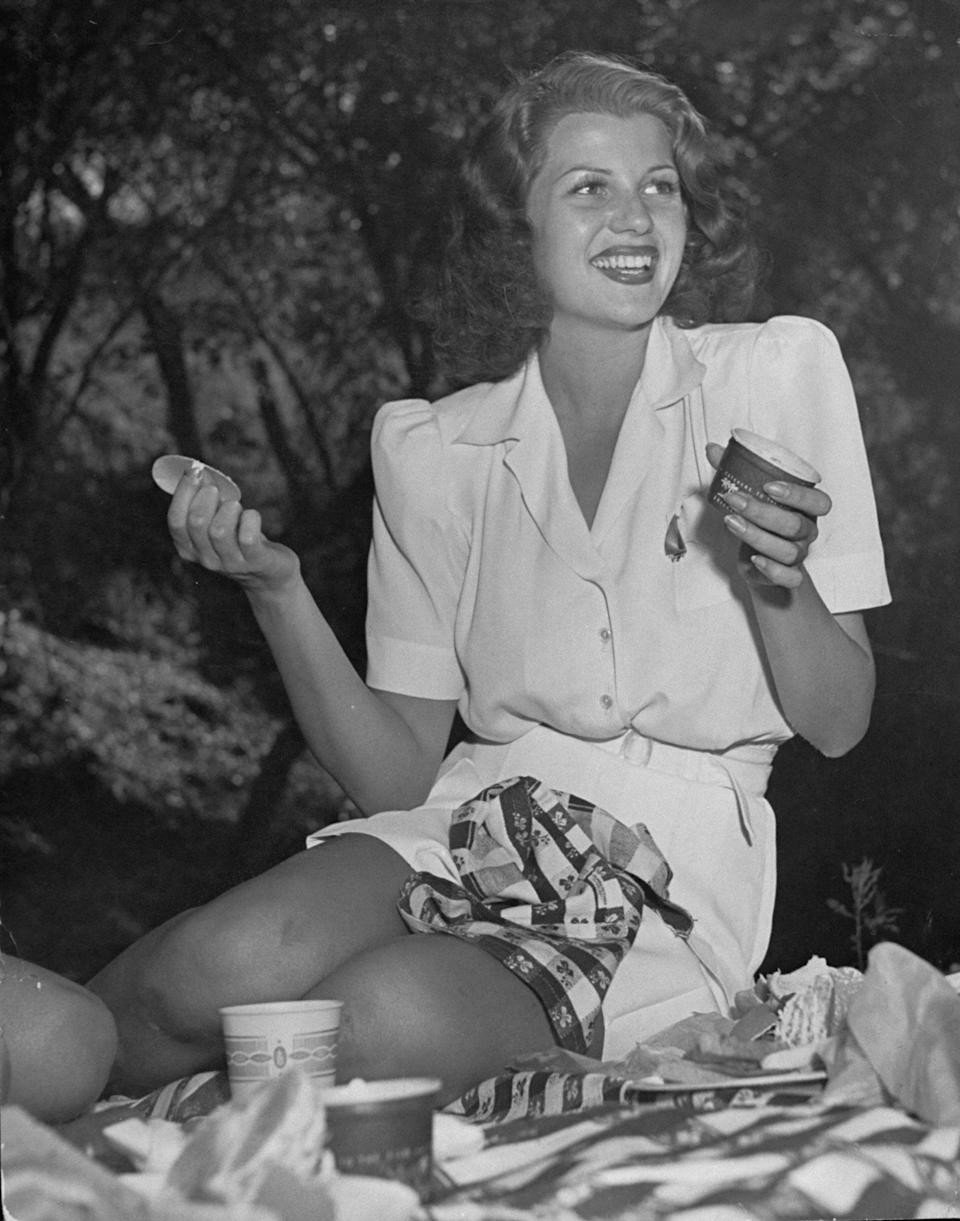 Actress Rita Hayworth, dressed in a white playsuit, sits on a picnic blanket in this undated photo.