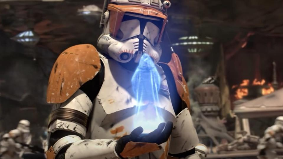 A clone trooper with white and orange gear looks at a hologram of Emperor Palpatine as a battle rages on behind him