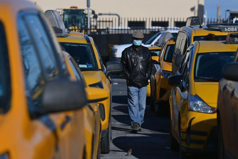 """A yellow cab taxi driver walks between cars as he waits in line at a taxi hold at LaGuardia Airport in New York City on February 04, 2021. - They were omnipresent on the streets of New York day and night, as emblematic of the Big Apple as the Empire State Building or Yankees caps. But the pandemic has made yellow taxis scarce and facing an uncertain future. On a February morning in a parking lot near La Guardia airport, a few dozen of the yellow cabs patiently queue in the freezing cold to catch a fare from one of the terminals. """"This lot used to be full with hundreds of cabs and even a line outside,"""" says 65-year-old Joey Olivo, recalling the days before coronavirus. (Photo by Angela Weiss / AFP)"""