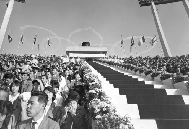 FILE - In this Oct. 10, 1964, file photo, five interlocking Olympic rings are thrown high in the sky by jet planes drift over the stadium during the opening ceremonies for the 1964 Olympics at the National Stadium in Tokyo. Tokyo used its famous 1964 Olympics to show off a miraculous recovery from defeat in World War II. For the 2020 Summer Olympics the Japanese capital will use the games to showcase a clean, safe, and innovative city with great shopping and nightlife. (AP Photo/File)