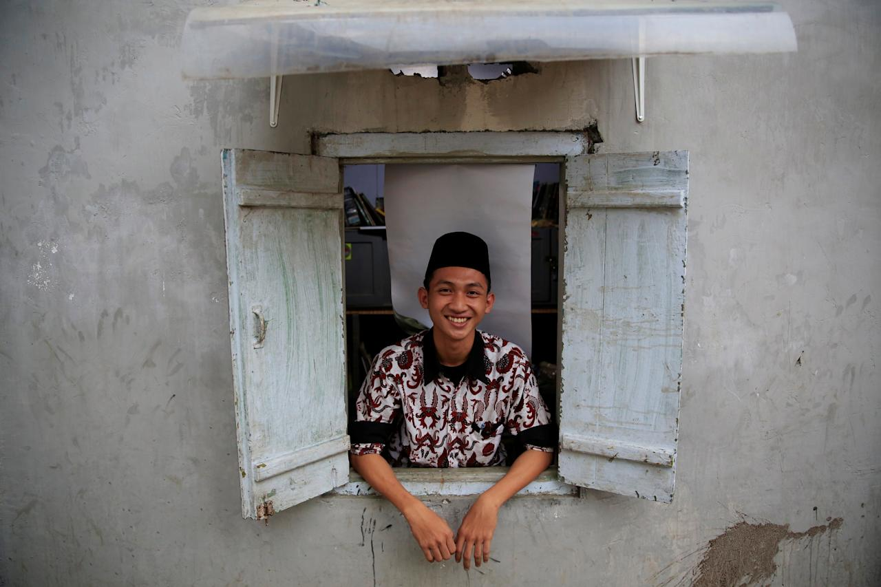 <p>A student poses for a photograph as he looks out from a dormitory window at Lirboyo Islamic boarding school in Kediri, Indonesia, May 19, 2018. (Photo: Beawiharta/Reuters) </p>