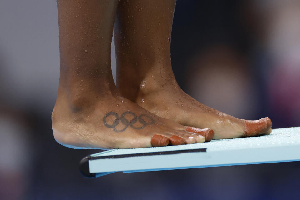 <p>A tattoo of the Olympic rings is pictured on the foot of Canada's Jennifer Abel as she prepares to compete in the women's synchronised 3m springboard diving final event during the Tokyo 2020 Olympic Games at the Tokyo Aquatics Centre in Tokyo on July 25, 2021. (Photo by Odd ANDERSEN / AFP) (Photo by ODD ANDERSEN/AFP via Getty Images)</p>