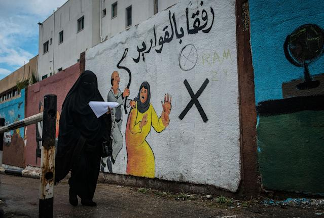 <p>A woman walks by a mural discouraging domestic violence outside if Al-Shifa hospital. According to a 2012 study, some 37% of women are subjected to domestic violence by their husbands. (Photograph by Monique Jaques) </p>