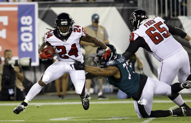 Atlanta Falcons' Devonta Freeman (24) tries to get away from Philadelphia Eagles' Michael Bennett (77) during the first half of an NFL football game Thursday, Sept. 6, 2018, in Philadelphia. (AP Photo/Michael Perez)