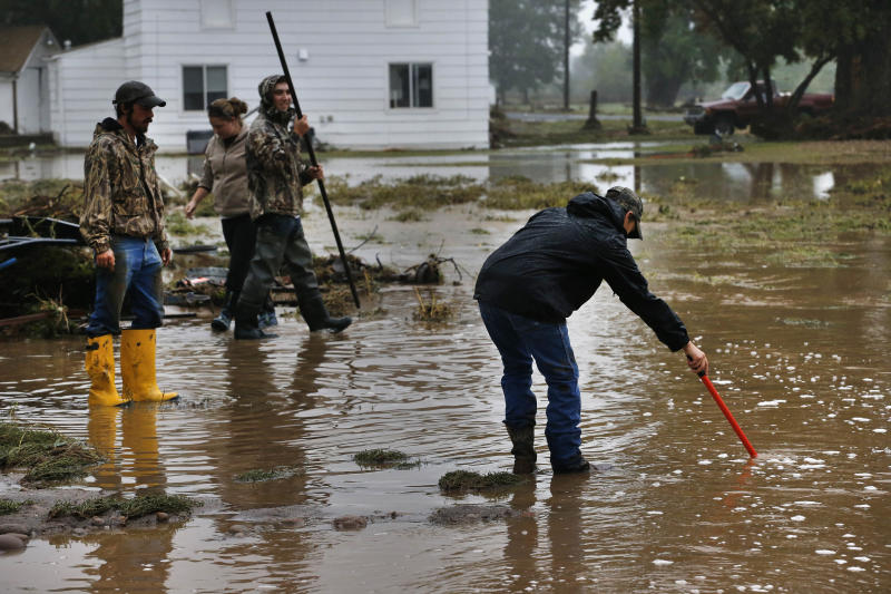 CORRECTS SPELLING OF CITY TO HYGIENE INSTEAD OF HYGEINE - Local residents, left to right, Tyler Sadar, Miranda Woodard, Joey Schendel, and Levi Wolfe help salvage and clean property in an area inundated after days of flooding, in Hygiene, Colo., Monday Sept. 16, 2013. Searches continue for missing people in isolated Colorado mountain towns. (AP Photo/Brennan Linsley)