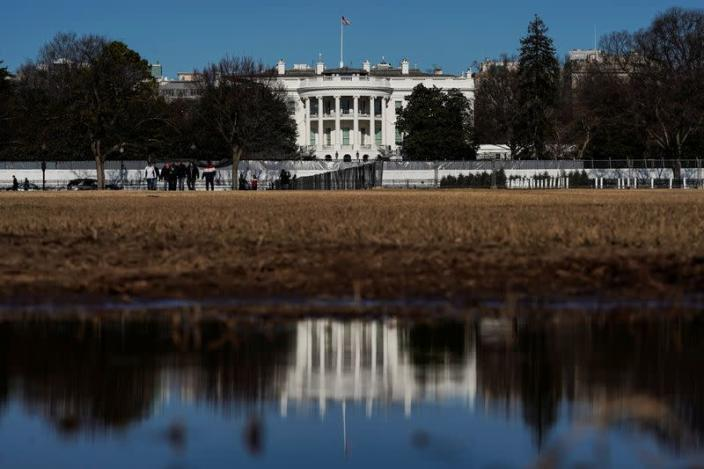 The White House is reflected in a puddle in Washington