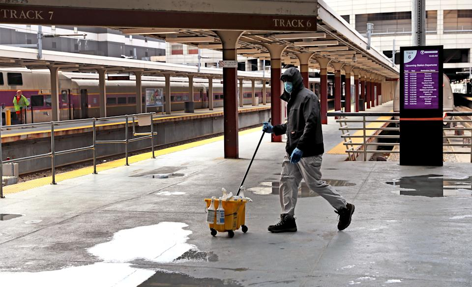 BOSTON, MA - APRIL 13: A custodian walks past empty train platforms at South Station in Boston during the COVID-19 pandemic on April 14, 2020. (Photo by David L. Ryan/The Boston Globe via Getty Images)