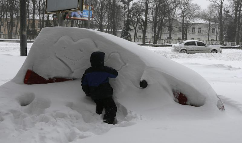 A boy draws on a snow-covered car in Kiev, Ukraine, Saturday, March 23, 2013. Heavy snow storms from the Balkan region have been stricken Ukraine since Friday afternoon, in a last winter attack at the end of the first spring month. (AP Photo/Efrem Lukatsky)