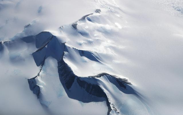 <p>Mountains peek through land ice as seen from NASA's Operation IceBridge research aircraft in the Antarctic Peninsula region on Oct. 31, 2017, above Antarctica. (Photo: Mario Tama/Getty Images) </p>