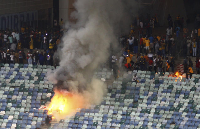 A fire burns in the stands at the Moses Mabhida stadium in Durban, South Africa after violence broke out at a soccer game when hundreds of fans ripped up parts of the stadium, invaded the pitch, and assaulted at least one security guard. (AP Photo)