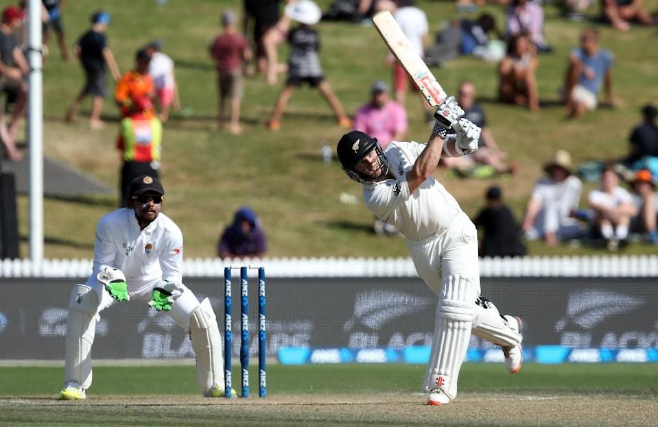 Kane Williamson of New Zealand plays a shot (R) in front of Dinesh Chandimal of Sri Lanka (L) on day three of the second Test in Hamilton on December 20, 2015 (AFP Photo/Michael Bradley)