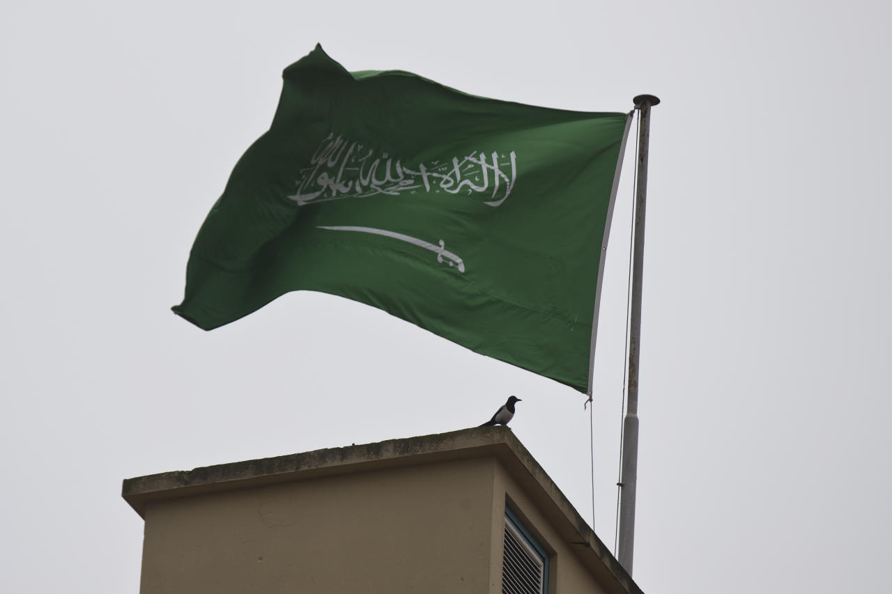 A bird sits by a Saudi Arabia's flag on the roof top of Saudi Arabia's consulate in Istanbul, Sunday, Oct. 14, 2018. Writer Jamal Khashoggi vanished after he walked into the consulate on Oct. 2. (AP Photo/Petros Giannakouris)