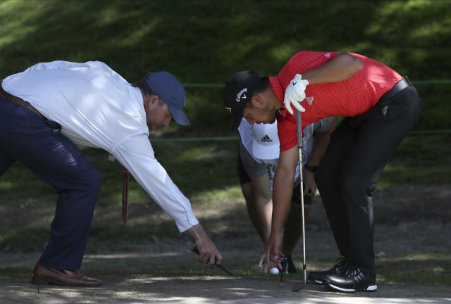 Xander Schauffele of the United States, right, places his ball after dropping it near the first green during the first round of the WGC-Mexico Championship golf tournament, at Chapultepec Golf Club in Mexico City, Mexico City, Thursday, Feb. 20, 2020.(AP Photo/Fernando Llano)