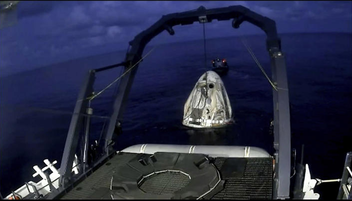 In this image taken from SpaceX video a SpaceX capsule carrying four people is lifted from the Atlantic Ocean off the Florida coast onto a recovery vessel, Saturday, Sept. 18, 2021. The all-amateur crew was the first to circle the world without a professional astronaut. (SpaceX via AP)