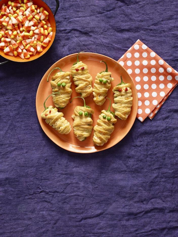 """<p>You're wearing a costume, so why shouldn't your food too? Transform your cheesy jalapeño poppers into little mummy bites. </p><p><em><strong><a href=""""https://www.womansday.com/food-recipes/food-drinks/recipes/a56191/hot-pepper-mummies-recipe/"""" rel=""""nofollow noopener"""" target=""""_blank"""" data-ylk=""""slk:Get the Mummy Jalapeño Poppers recipe."""" class=""""link rapid-noclick-resp"""">Get the Mummy Jalapeño Poppers recipe.</a></strong></em></p>"""