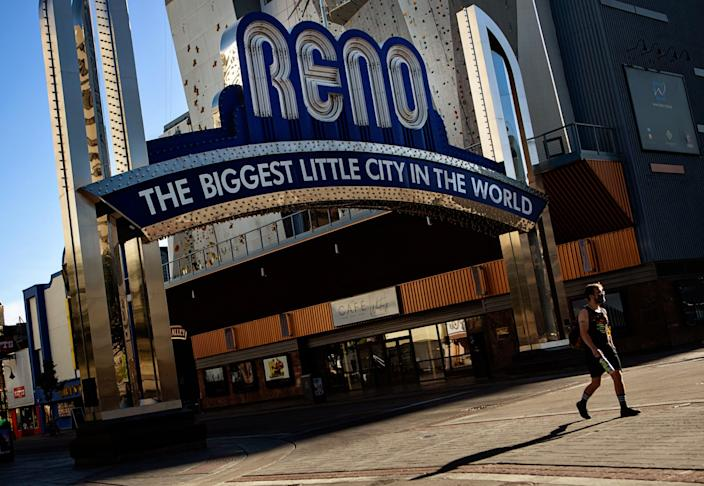 A pedestrian passes by The Reno Arch