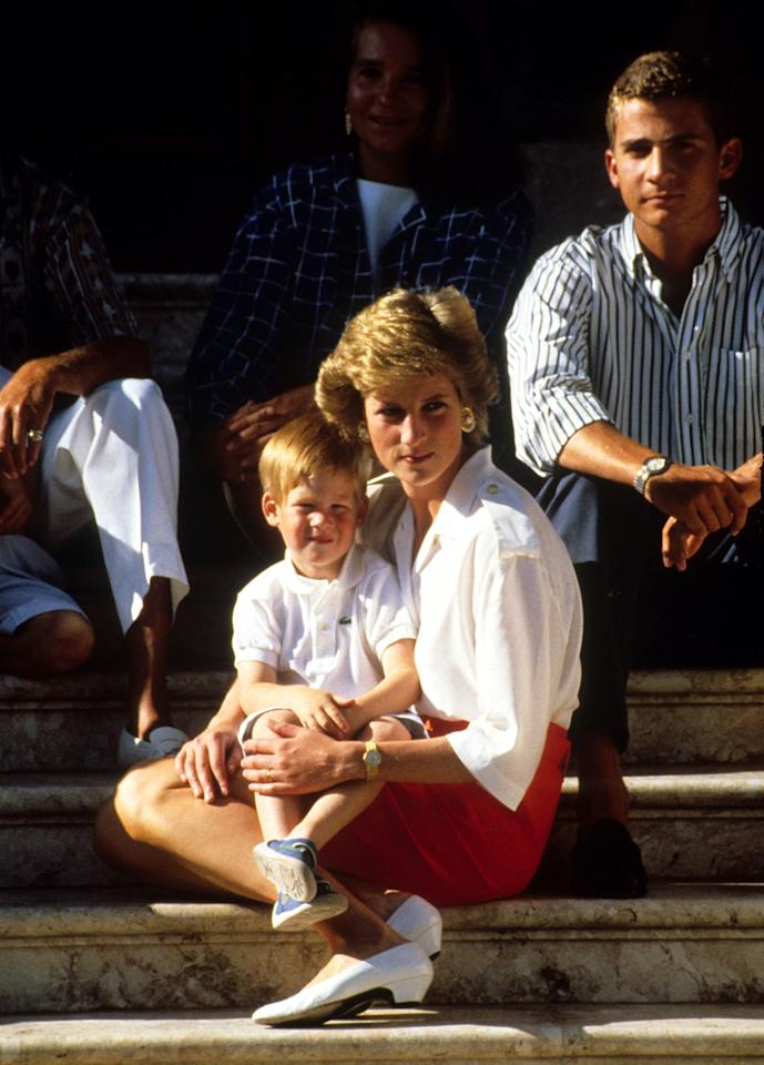<p>Diana holds Harry on her knee as the family holiday in Majorica, Spain in August 1988 (PA) </p>