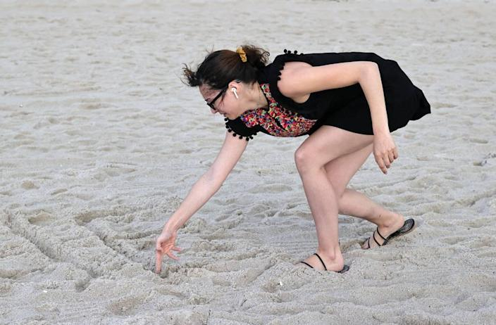 Fayzah Bushnaq, 27, from Virgina writes a message on the sand close to the Champlain Towers South Condo in Surfside, Florida, Friday, June 25, 2021. The apartment building partially collapsed on Thursday, June 24.