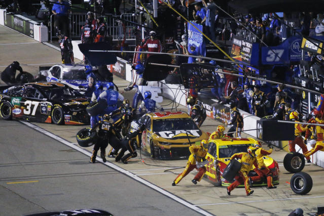 Joey Logano, right, and others make pit stops during the NASCAR Cup Series auto race at Richmond Raceway in Richmond, Va., Saturday, Sept. 21, 2019. (AP Photo/Steve Helber)
