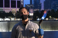 """Kevin Hansen, an engineer at the September 11 Memorial, poses with a torch he uses to clean and burnish the names cut into the metal plates that border the south pool, Wednesday, Aug. 4, 2021, in New York. Hansen says of the work he does, """"It's important to me. It's a sign that it's something I can do. I can give back and say this is something that cannot be forgotten. This is a sign that we all came together back in 2001. This is my giveback of patriotism and this (event) cannot be forgotten."""" (AP Photo/Mark Lennihan)"""