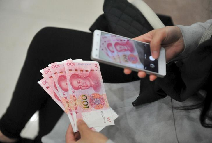 A woman takes pictures of new 100 yuan banknotes she withdrew from a bank in Hangzhou