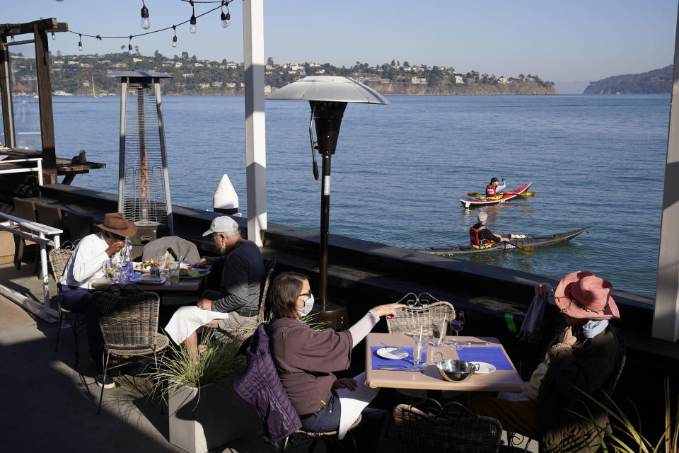 People dine outdoors at The Trident restaurant Friday, Dec. 4, 2020, in Sausalito, Calif. The health officers in six San Francisco Bay Area regions have issued a new stay-at-home order as the number of virus cases surge and hospitals fill. The changes announced Friday will take effect in most of the area at 10 p.m. Sunday and last through Jan. 4. It means restaurants will have to close to indoor and outdoor dining, bars and wineries must close along with hair and nail salons and playgrounds. (AP Photo/Eric Risberg)