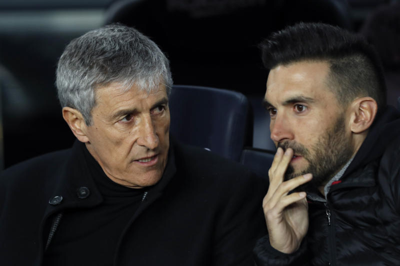 Barcelona's head coach Quique Setien talks with assistant coach Eder Sarabia, right, on the bench during a Spanish La Liga soccer match between Barcelona and Granada at Camp Nou stadium in Barcelona, Spain, Sunday, Jan. 19, 2020. (AP Photo/Joan Monfort)