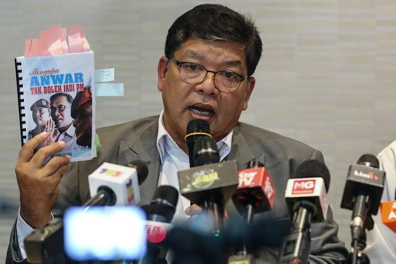 Johari holds up a copy of 'Mengapa Anwar Tak Boleh Jadi PM' during a press conference at PKR's headquarters in Petaling Jaya June 19, 2019. — Picture by Yusof Mat Isa