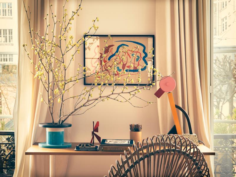 In the salon, a 1958 gouache artwork by Italian artist Giulio Turcato, from 1958. To the left is a vase by Ettore Sottsass; his Tahiti lamp for Memphis is on the right. The rattan chair is by Franco Albini.