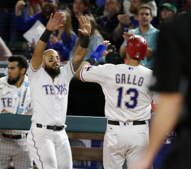Texas Rangers Rougned Odor, left, congratulates Joey Gallo (13) after Gallo scored against the Houston Astros during the seventh inning of a baseball game Friday, March 30, 2018, in Arlington, Texas. (AP Photo/Michael Ainsworth)